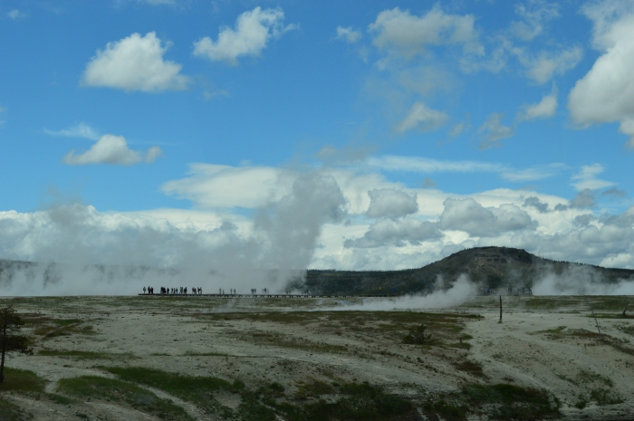 Tiny people in the steam from a geyser basin